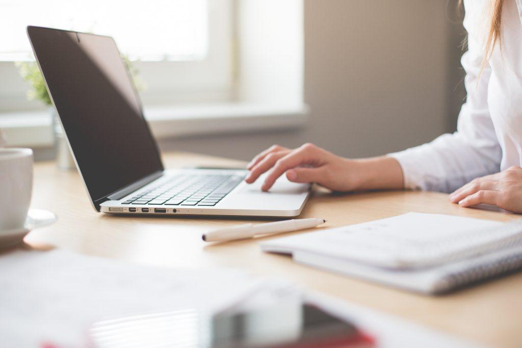 Frau sitzt fokussiert an einem Laptop  und vor ihr liegen Zettel und Stift.