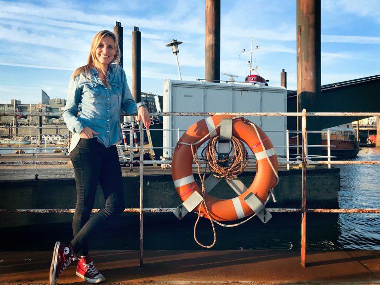 Marina vor Hafenkulisse mit Rettungsring